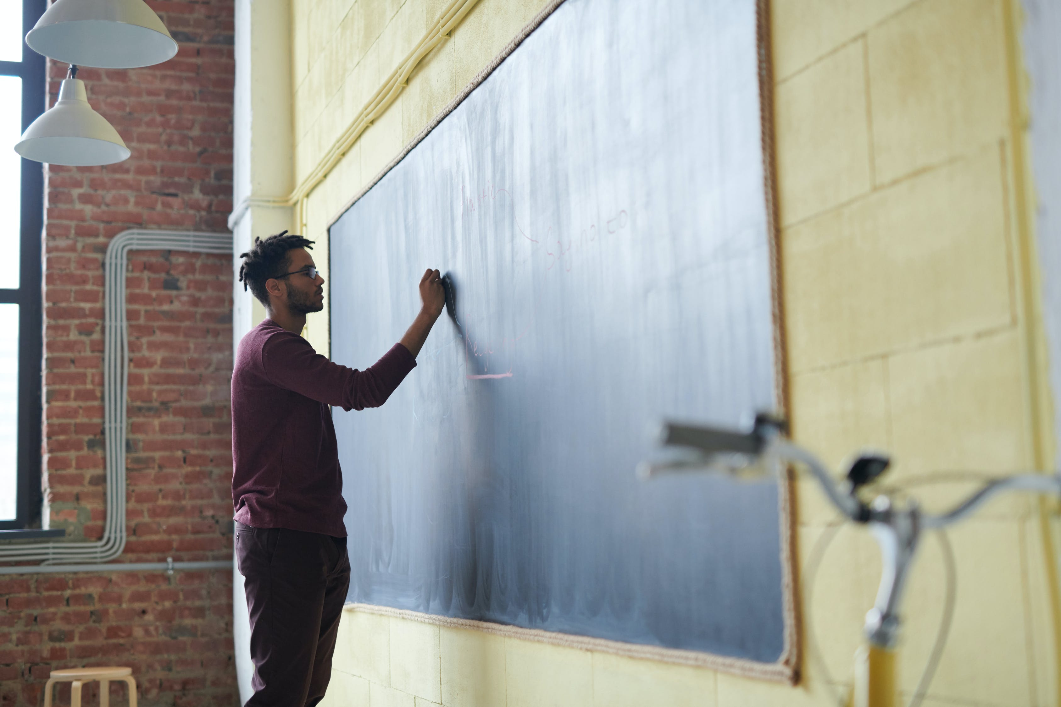 Image of a man standing before a blackboard. He is writing on the board with chalk.