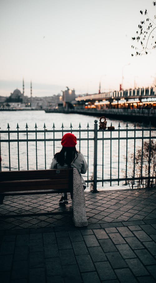 Unrecognizable woman contemplating city river under bridge in evening