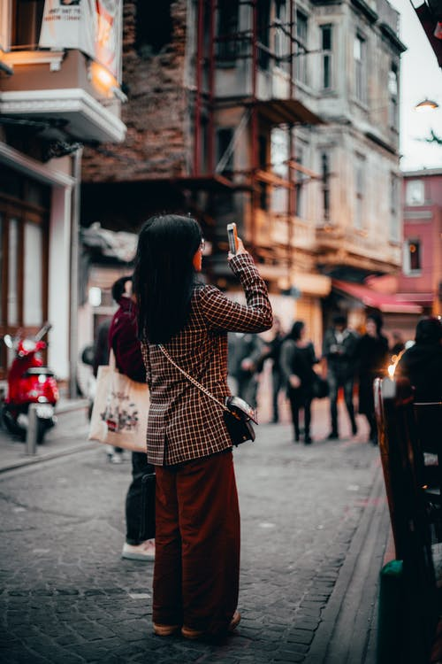 Selective Focus Photography of Woman Taking Photo While Standing on Alley