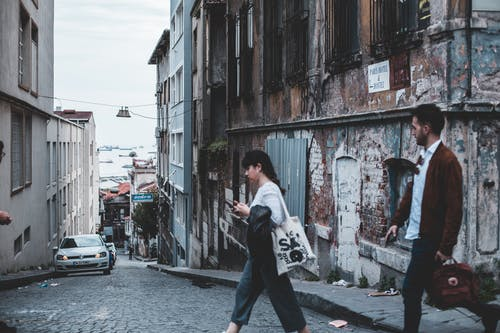 Man and Woman Crossing A City Street With An Old Abandoned Building In The Corner