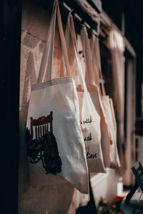Cloth Tote Bags With Assorted Prints Hanging On A Rack