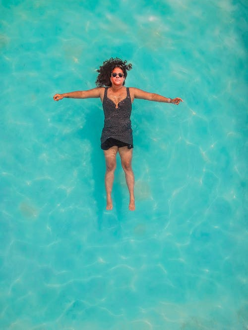 Top View Photo of Woman Floating on Water