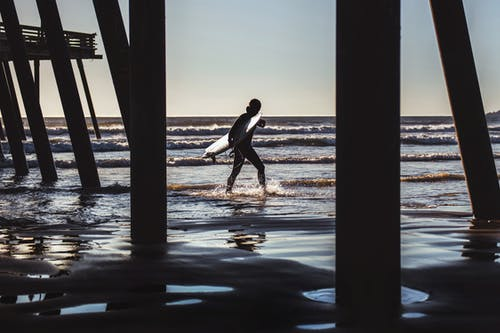 Surfer Walks Near Dock at the Beach