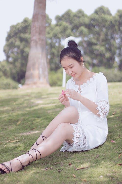 Immagine gratuita di ragazza asiatica, terreno erboso, vestito bianco