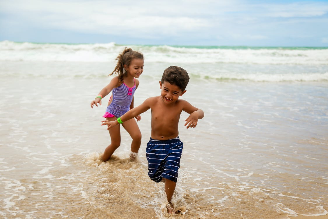 Photo of Children Smiling While Running on Seashore