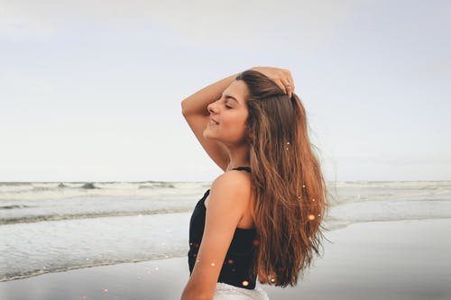 Side view of smiling young female with eyes closed wearing black top touching long dark hair standing against ocean