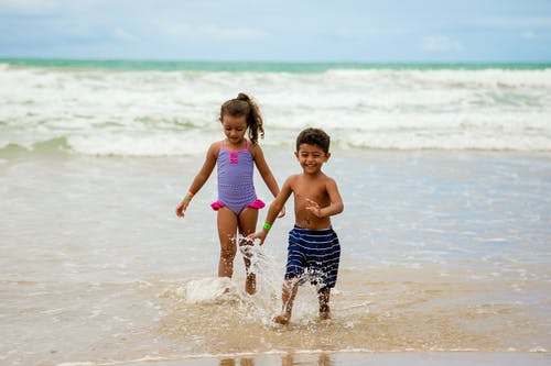 Children in swimwear running on beach