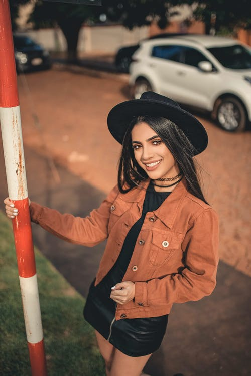 Selective Focus Photography of Smiling Woman Holding on Metal Tube
