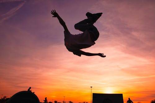 Person in White Shirt Jumping during Sunset