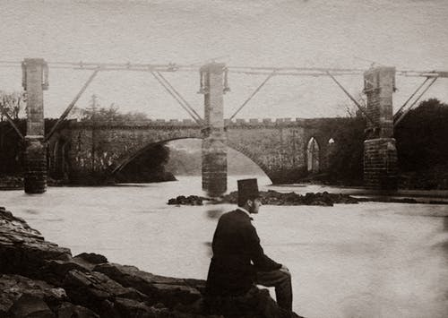 Grayscale Photo Man Wearing A Hat And Suit Sitting By The River Near A Bridge