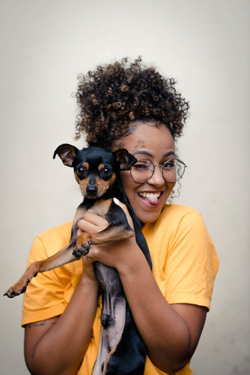 Woman in Yellow Top Carrying Short-coated Black and Brown Dog
