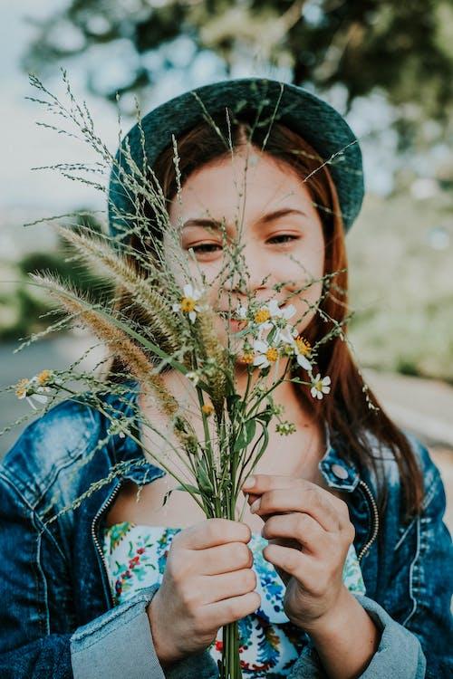 Woman in Blue Denim Jacket Holding Daisy Flowers