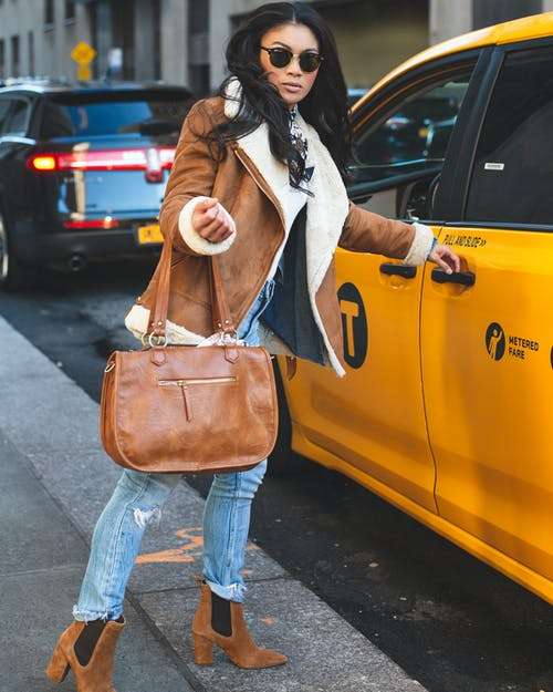 Woman in Brown Jacket and Blue Jeans Carrying Brown Tote Bag