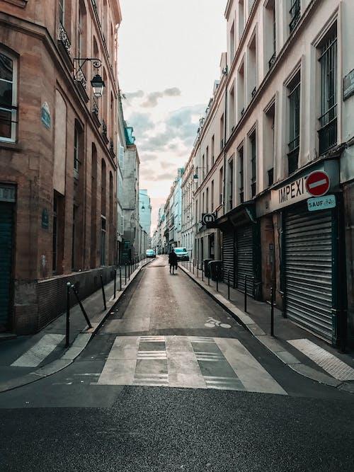 Empty Street Between Brown Concrete Buildings