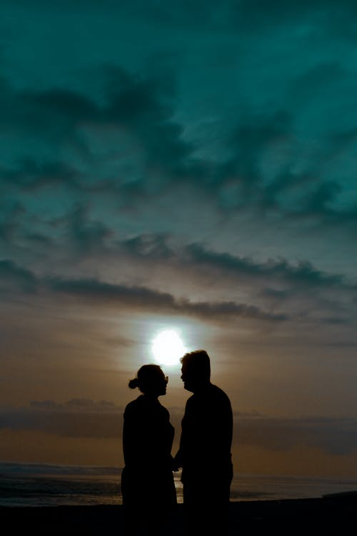 Silhouette of 2 Person Standing Under Cloudy Sky during Sunset