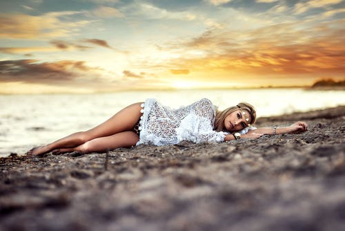 Woman in White Mini Dress Lying on Shore
