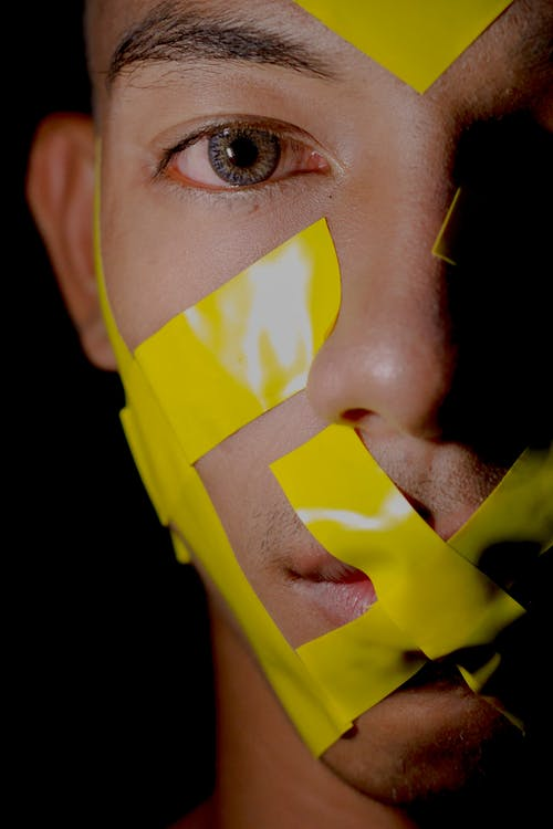 Man's Face With Yellow Adhesive Tapes