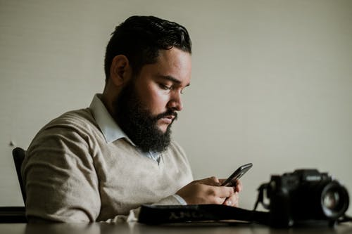 Man With Facial Hair Holds Smartphone