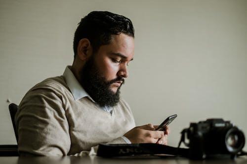Homme, à, Cheveux Faciaux, Tient, Smartphone