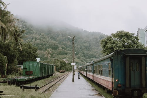 Person Standing  By An Old Train  In A Train Stop Close To A Mountain With Tick Vegetation