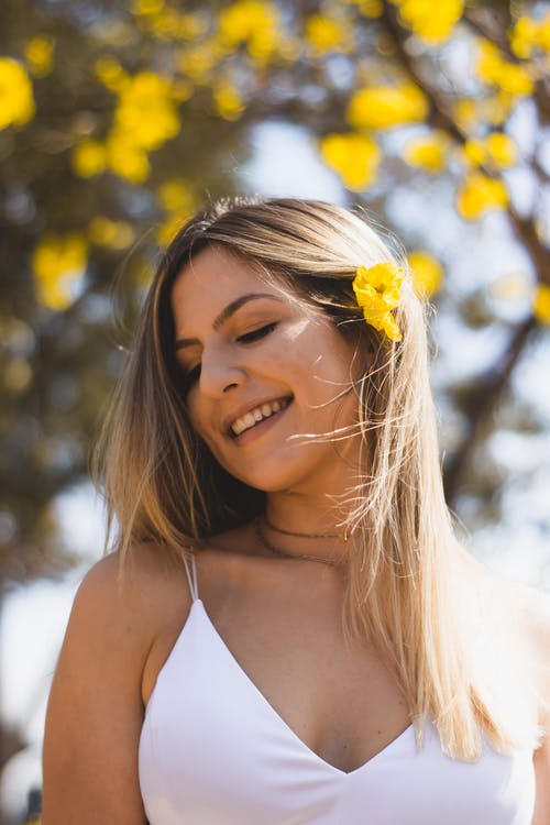 Woman Smiling With Yellow Flower on Her Hair