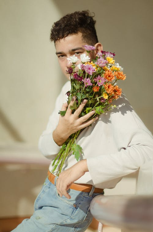 Selective-focus of Photography of Man in White Long-sleeved Shirt and Blue Denim Bottoms Holding Bouquet of Flowers