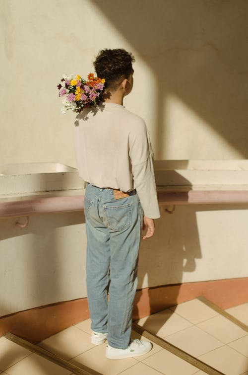 Back View Of A Young Man Carrying A Bouquet Of Flowers on His Shoulder