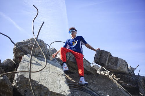 Low Angle Shot Of A Young Man In Colorful Active Wear Sitting On Top Of A Pile Of Rubble