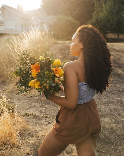 Woman in Gray Off-shoulder Top and Brown Shorts Holding Yellow Flower