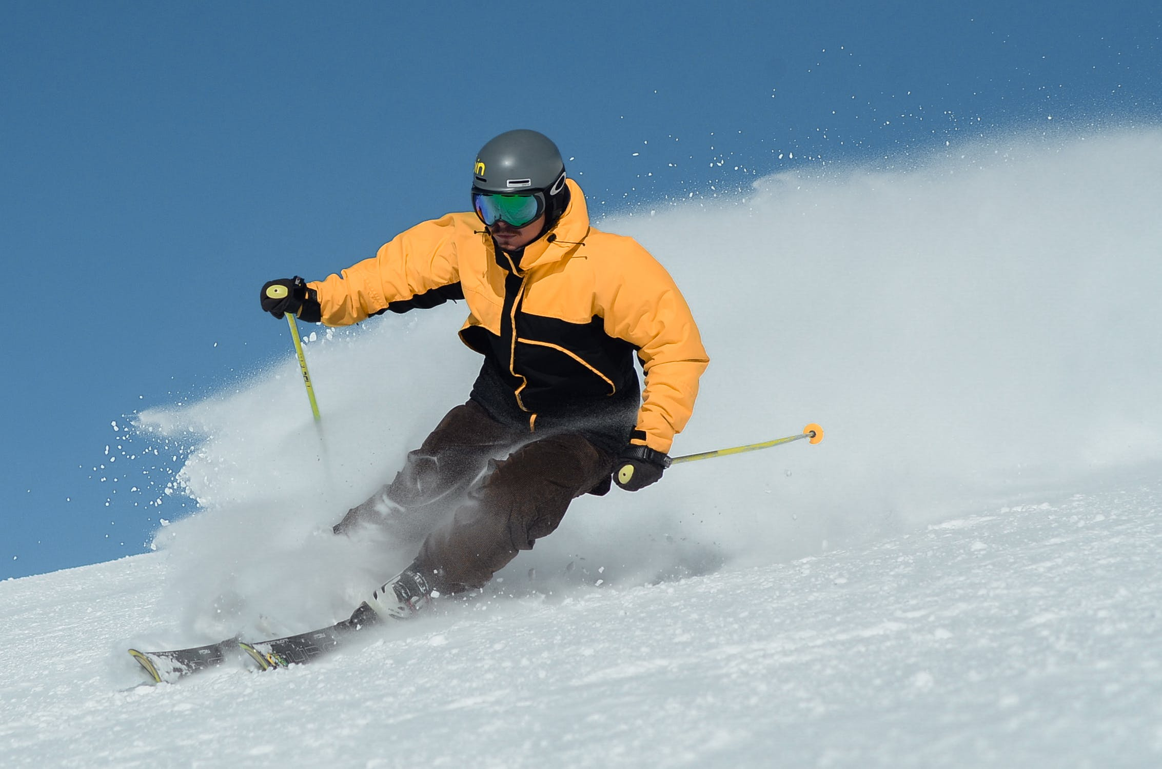 A man in a yellow jacket and ski gear skis down a snowy slope with a blue sky in the background