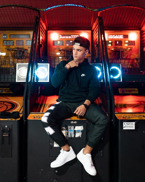 Young man in street style wear sitting on gaming machine