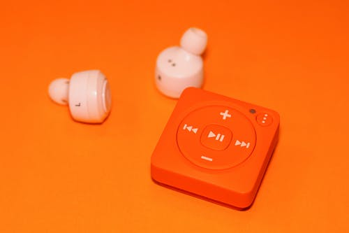 White Earphones Beside Orange Music Player