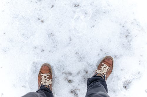 Person Wearing Brown Low-top Sneakers Standing on Snow-covered Floor