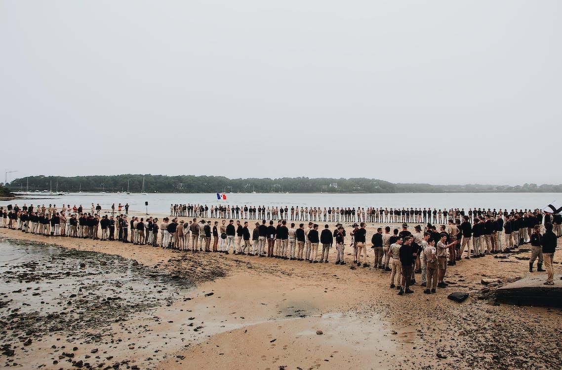 People Standing Beside Body of Water
