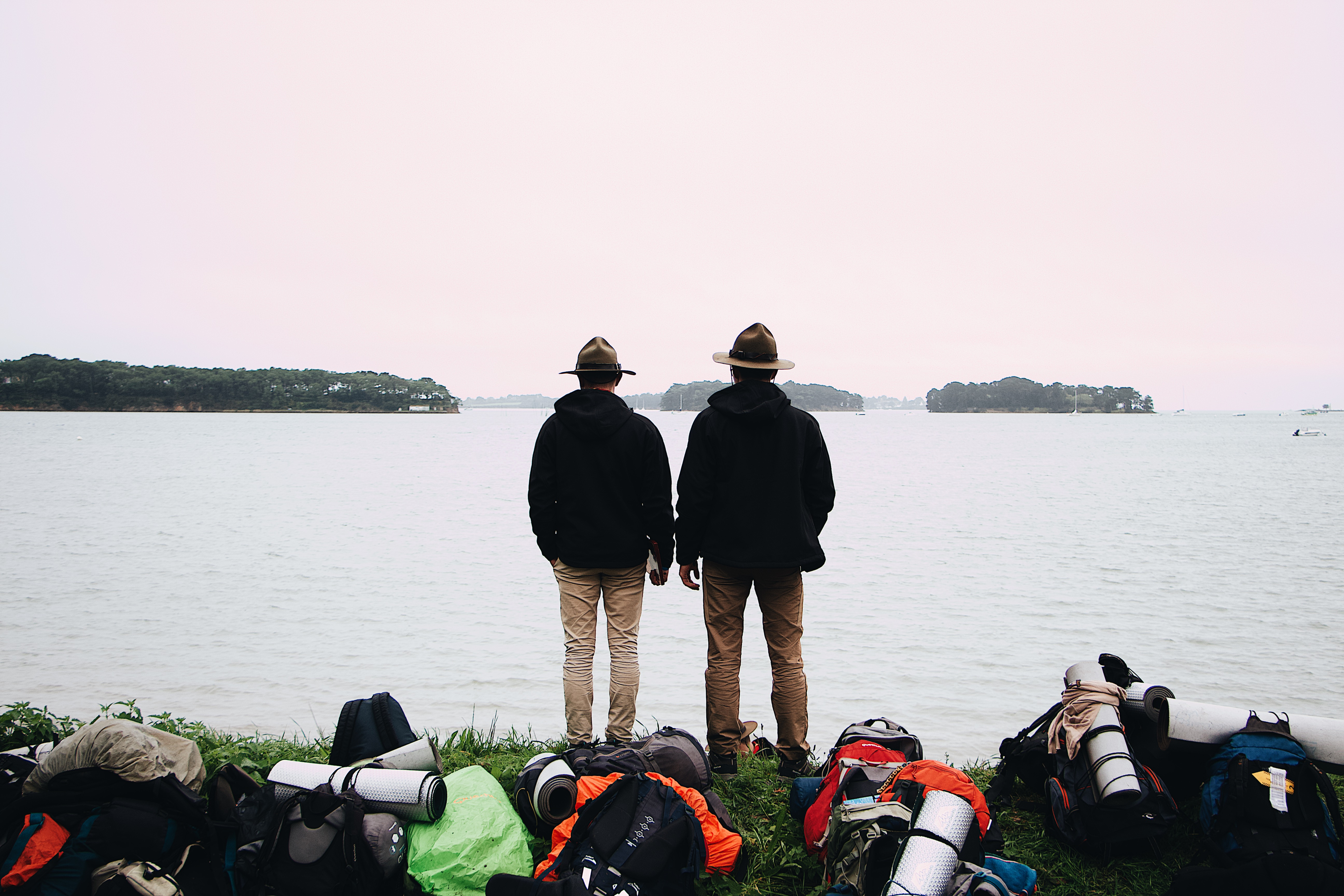 Two Men With Hats and Black Jackets Stand Near Body of Water