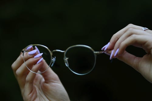 Photo of Person's Hand Holding an Eyeglasses Against Black Background