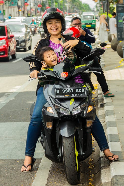 Free stock photo of happy, mother and child, riding, street photography