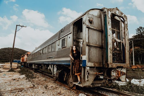 Woman in Black Top Standing on Gray and White Train Door