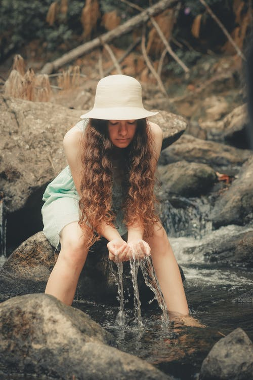Woman Sitting on Rock Holding Water