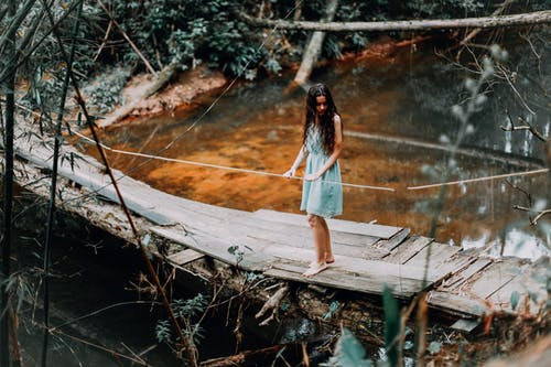 Woman Standing on Wooden Bridge
