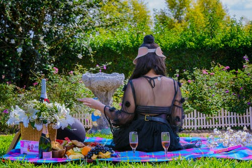 Back View Of A Woman In A Black Sheer Dress Picnicking In The Garden