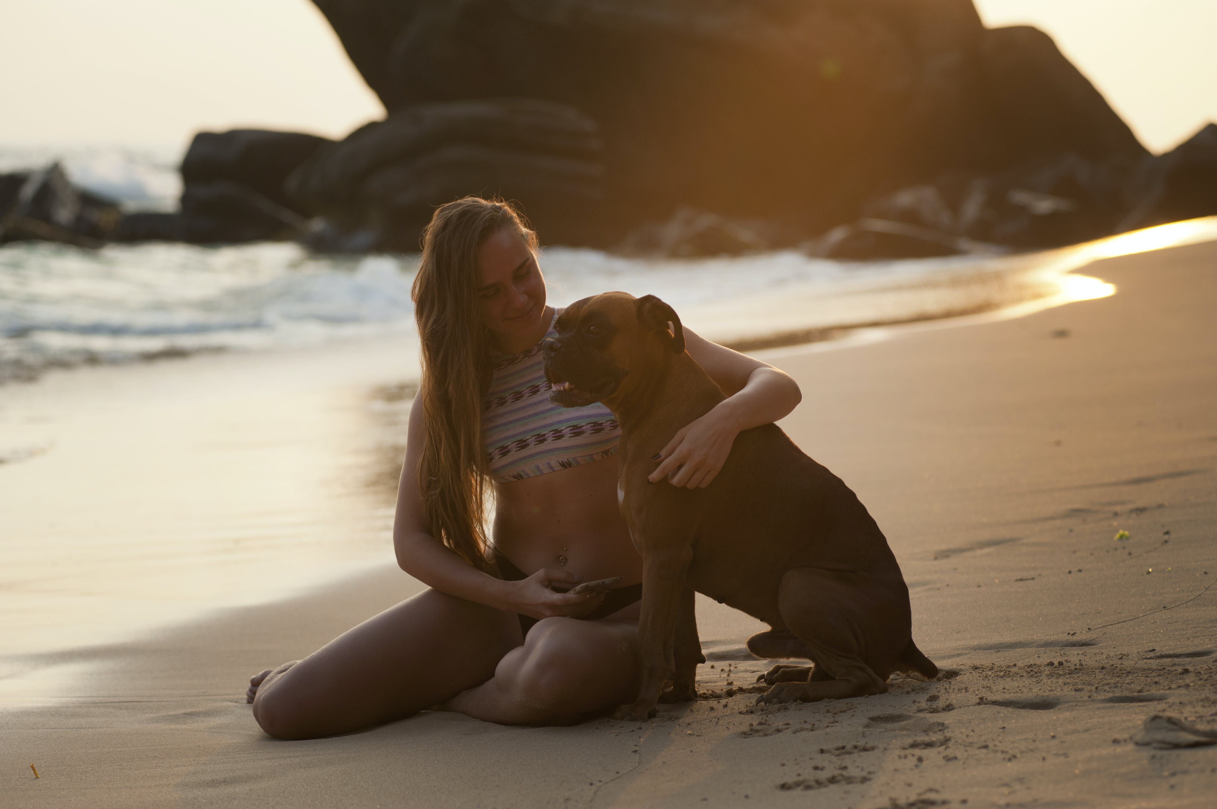 Woman Holding Boxer Dog on Beach Shore