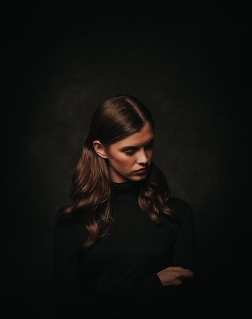 Photo of Woman in Black Turtleneck Sweater Posing In Front of Black Background While Looking Away