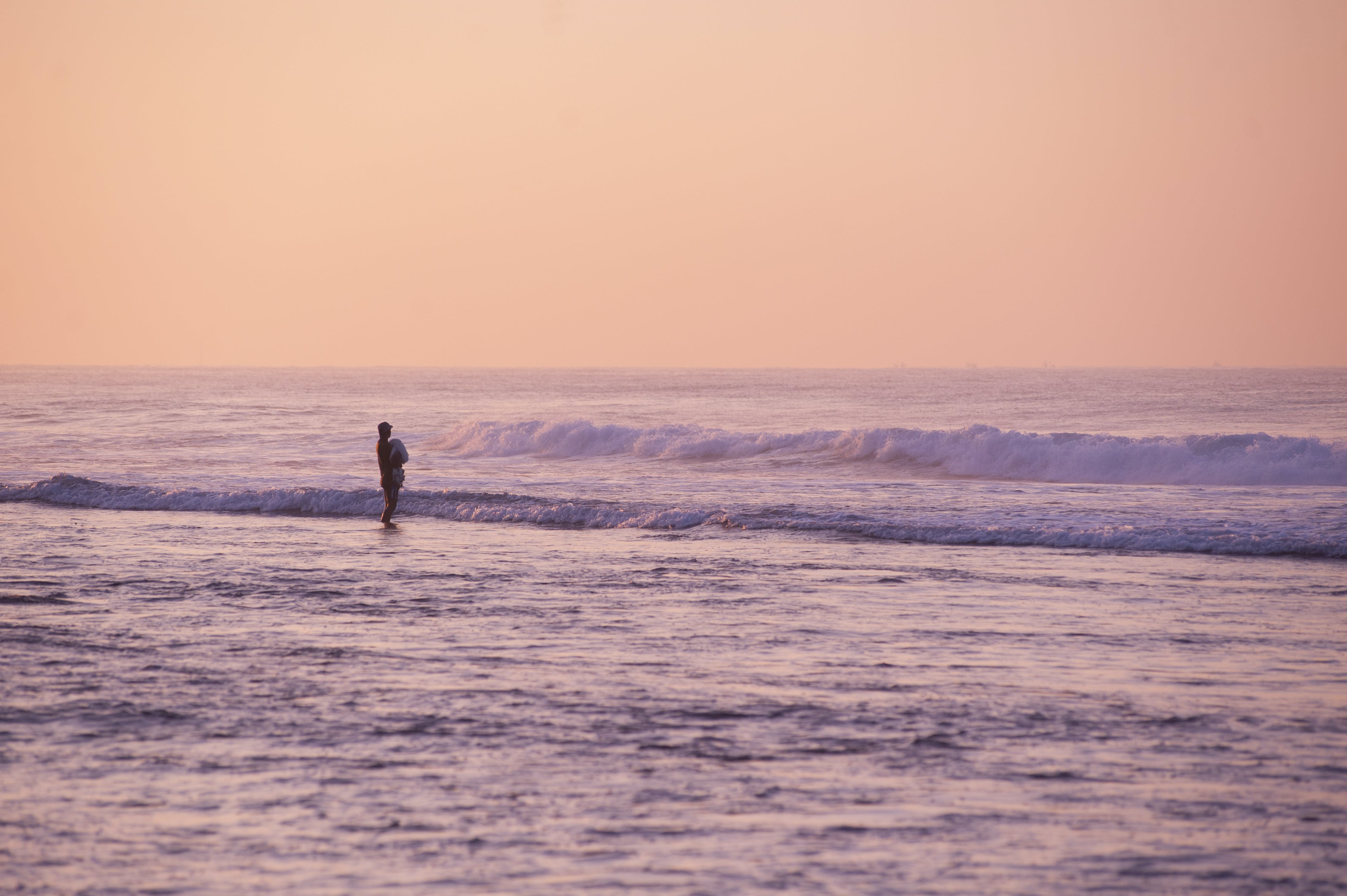 Person Standing on Seashore during Golden Hour
