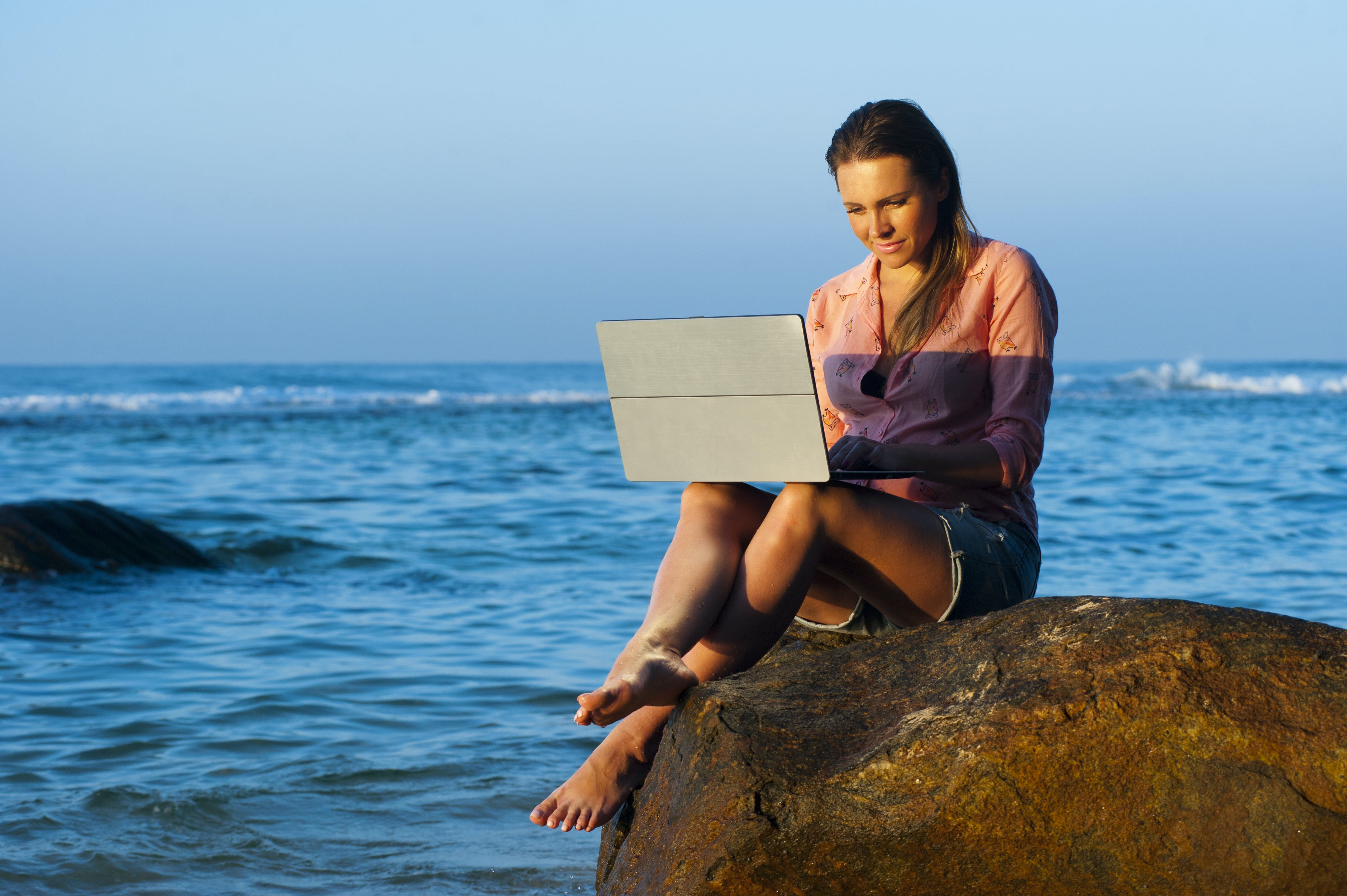 Woman Sitting on Brown Rock While Using Laptop