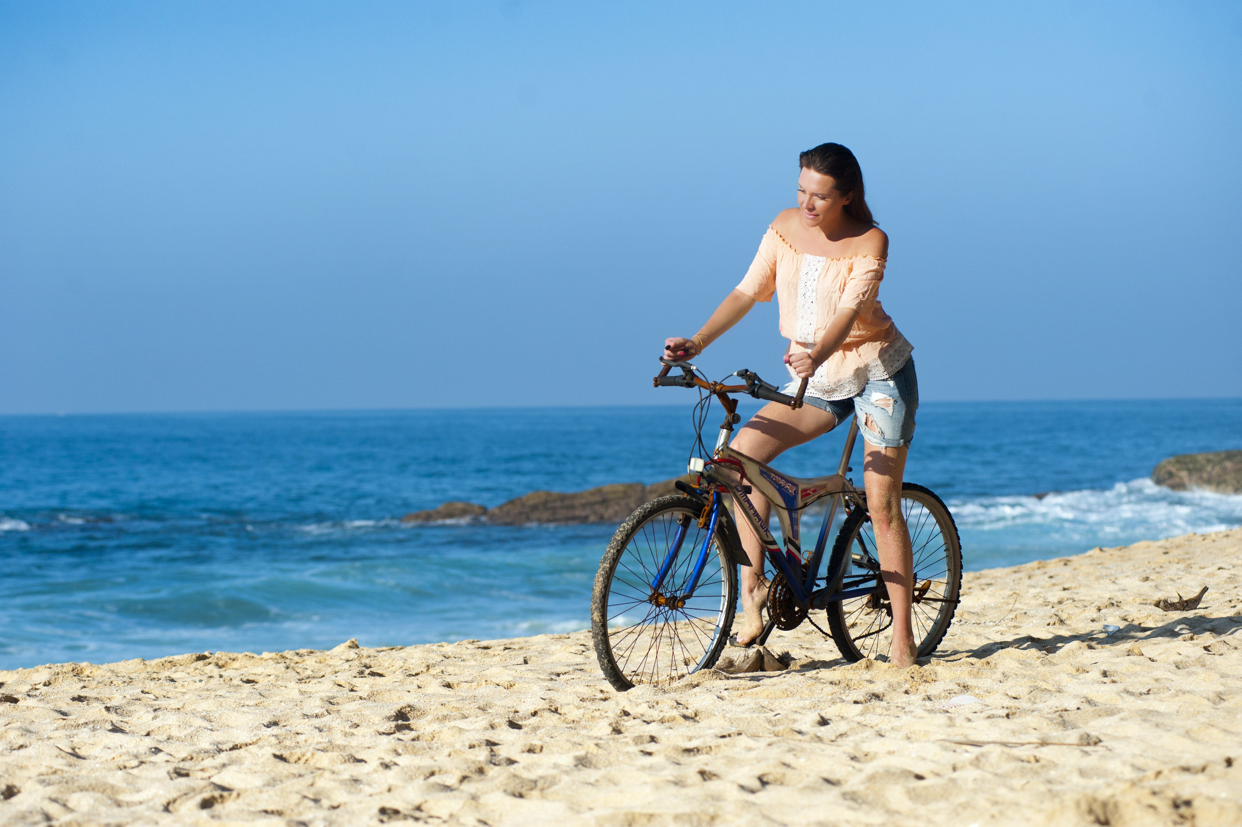 Woman Riding Bicycle by the Seashore