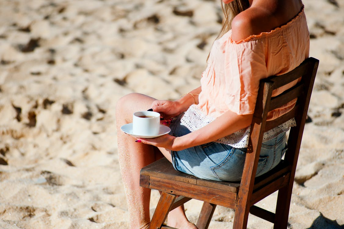 Woman Sitting on Chair While Holding Teacup