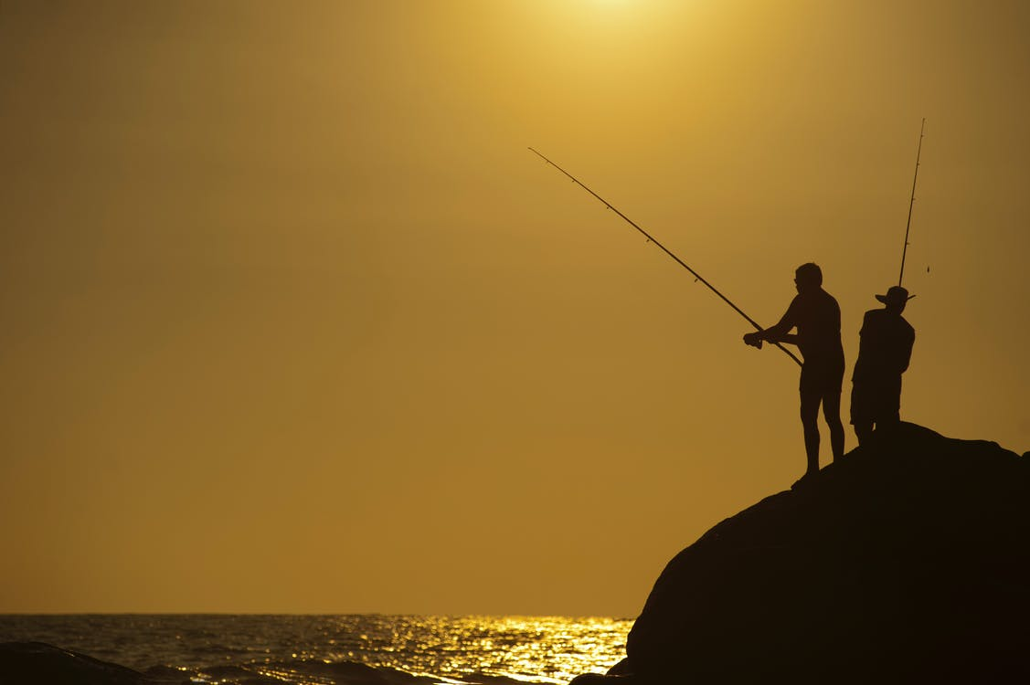 Silhouette Photo of Two Men Holding Fishing Rods Against Body of Water on Hill