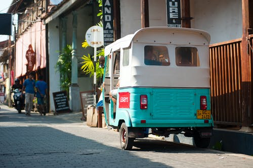 White and Teal Auto Rickshaw Beside Brown Wooden Rails