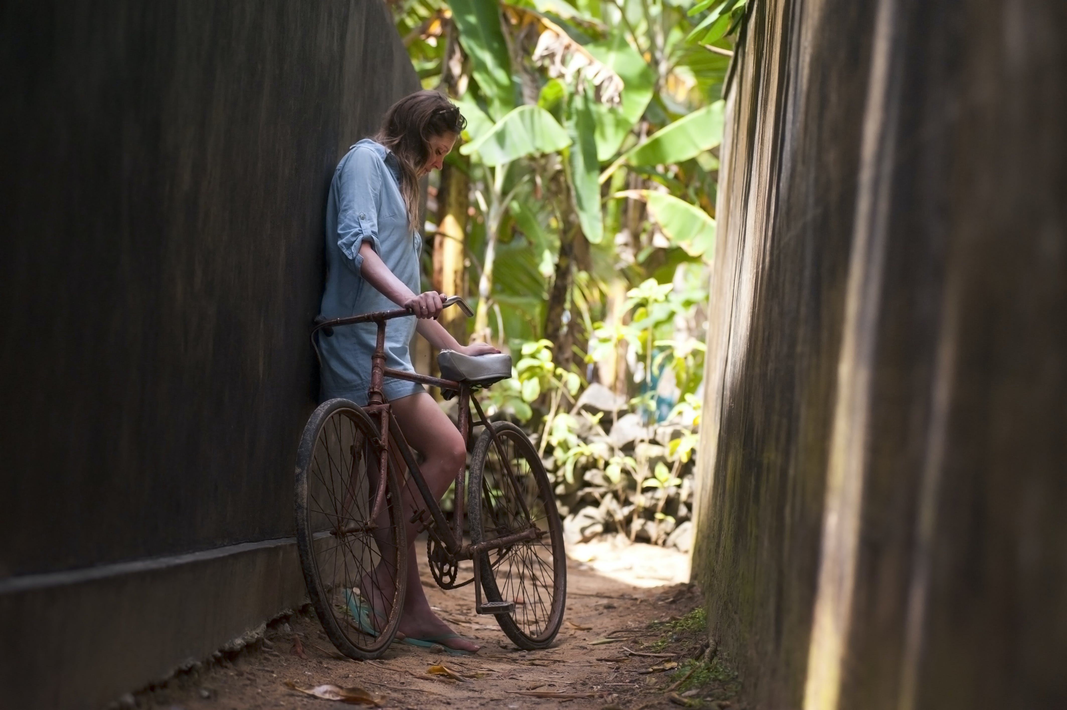 Woman Standing Beside Bike Leaning on Wall